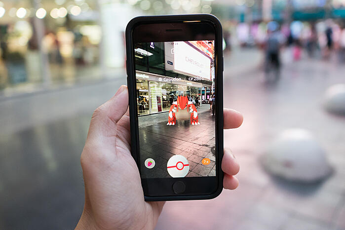 iPhone 7 held in one hand showing its screen with Pokemon Go Application